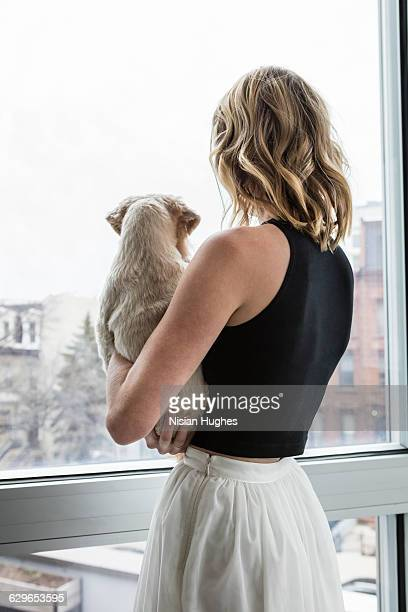 Woman looking out window holding her pet dog
