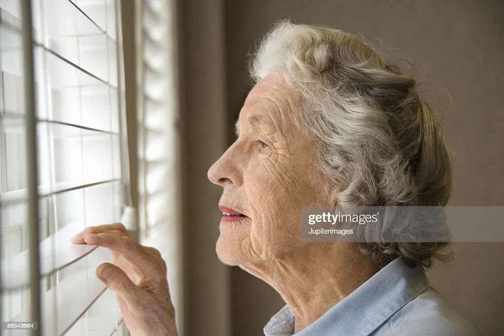 Woman looking out window : Stock Photo