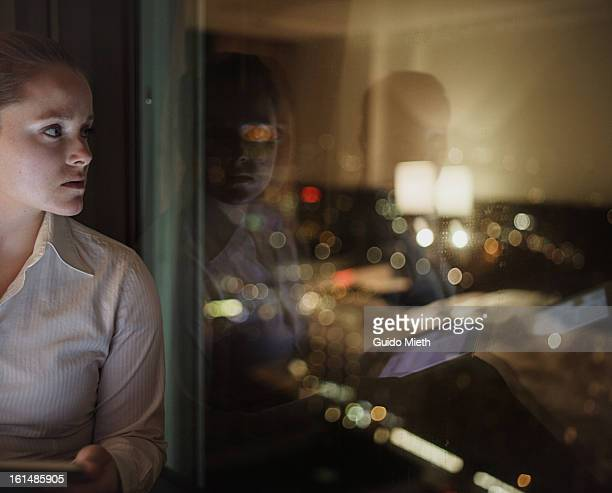 Woman looking out window with city lights.