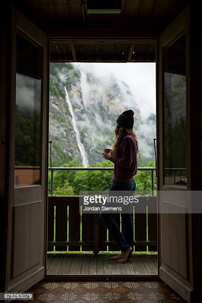 A woman looking out with a cup of coffee