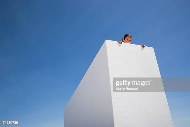 woman looking over edge of roof - curiosity stock pictures, royalty-free photos & images