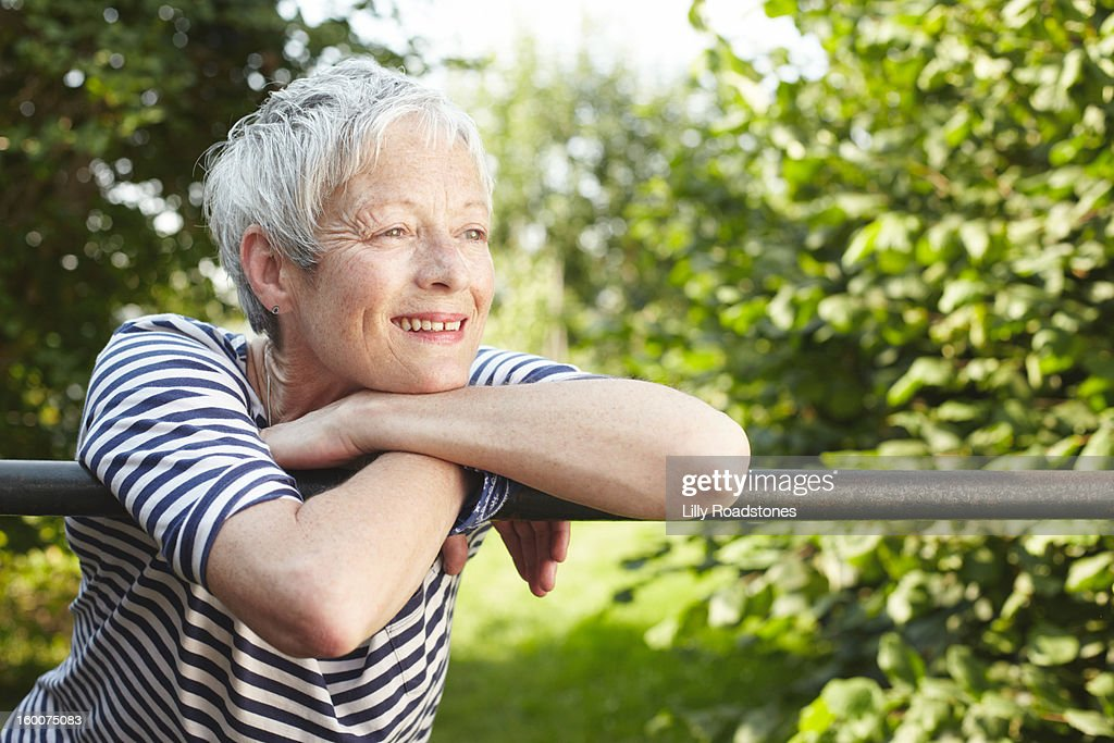 Woman looking over gate : Stock Photo