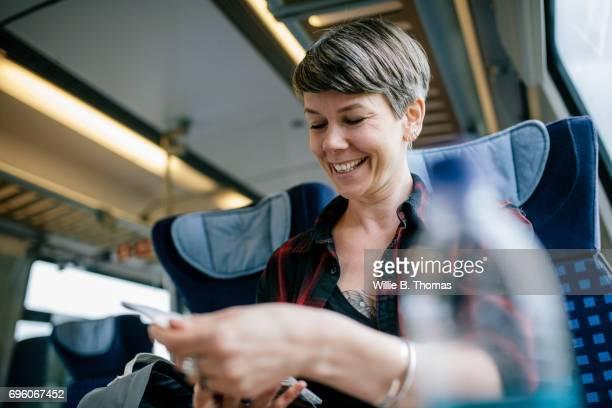 woman looking over map on train - zug stock-fotos und bilder