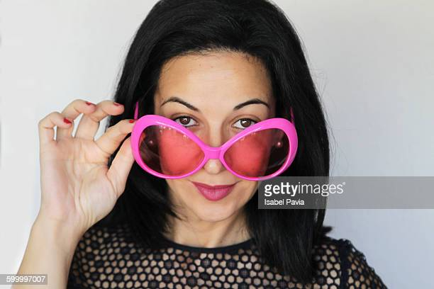 woman looking over pink glasses - thick rimmed spectacles - fotografias e filmes do acervo