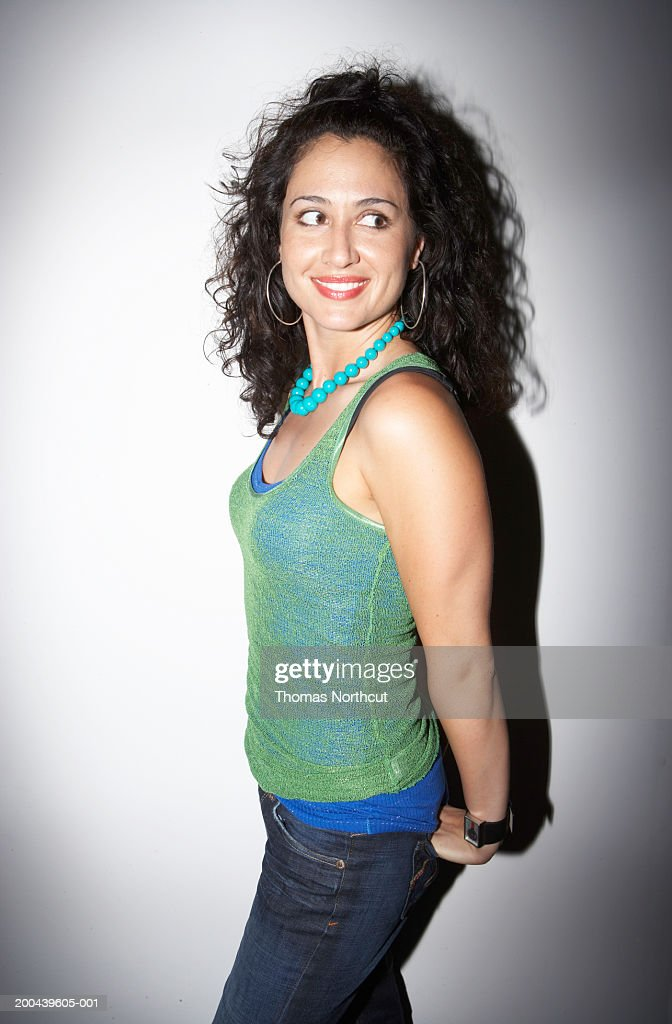 Woman looking over shoulder, smiling, side view : Stock Photo