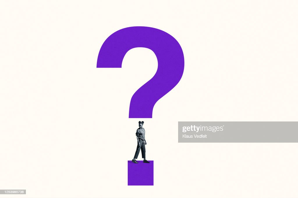 Woman looking over shoulder under question mark : Stock Photo