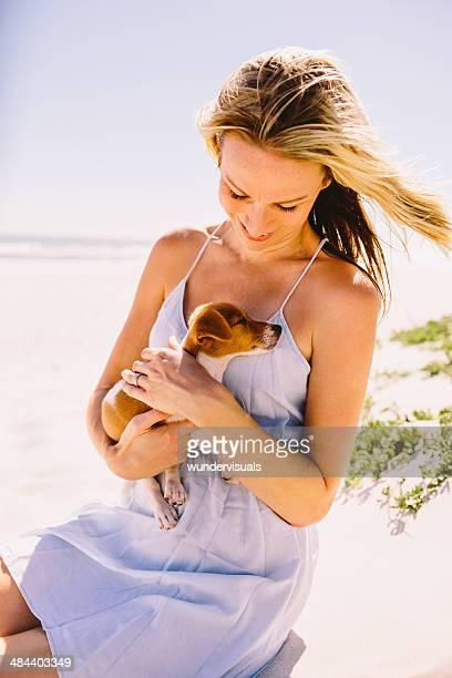 Frau schaut Welpen in den Armen beach