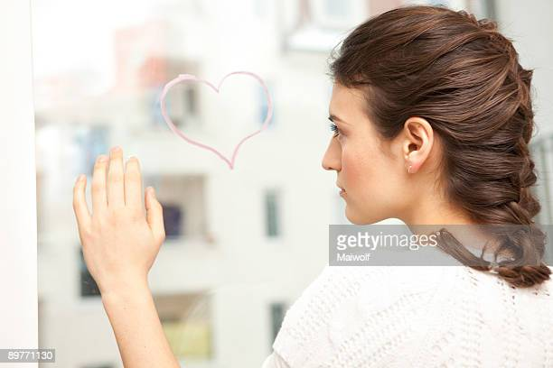 Woman looking sadly at a painted heart.