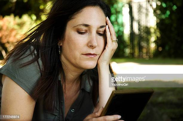 a woman looking sadly at a photograph  - death photos stock pictures, royalty-free photos & images