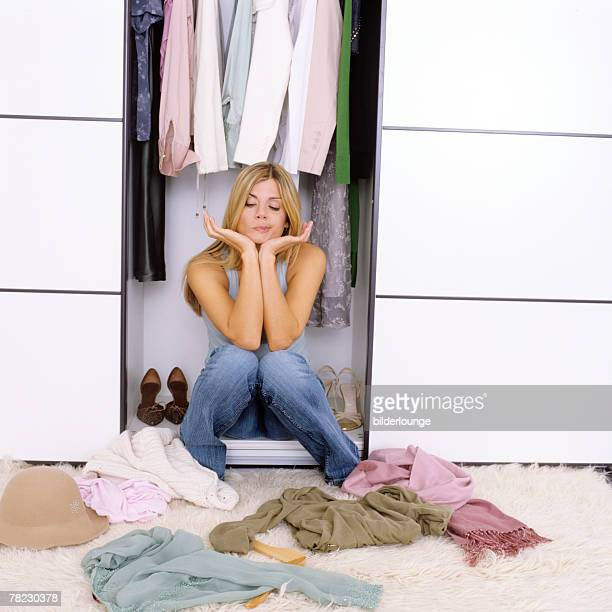 woman looking sceptical at assortment of clothes in front of her