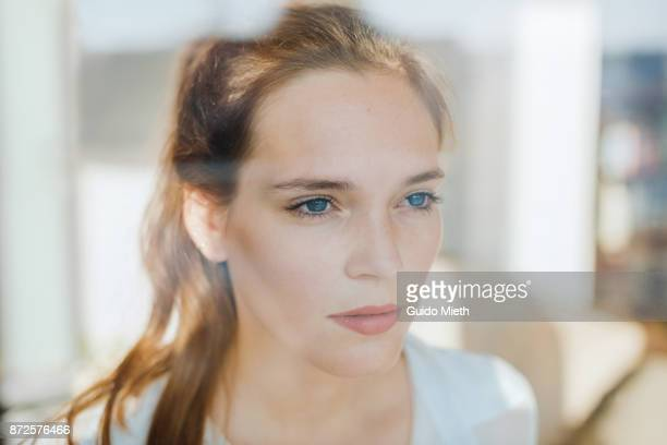 woman looking serious behind a window. - beleza natural imagens e fotografias de stock