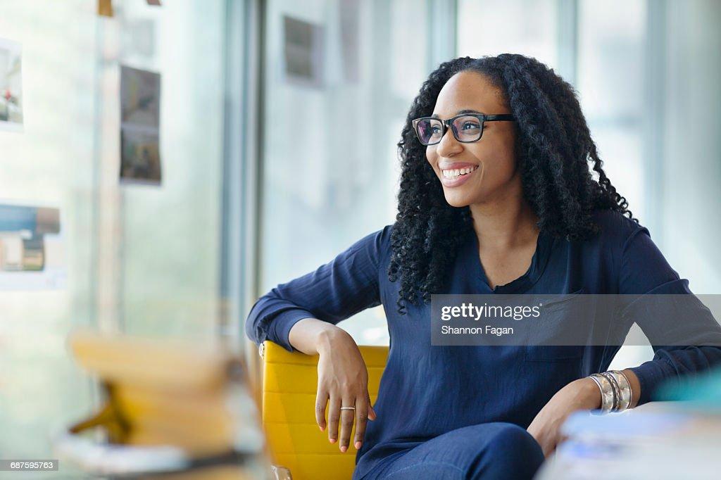 Woman looking sideways to window in design office : Stock Photo