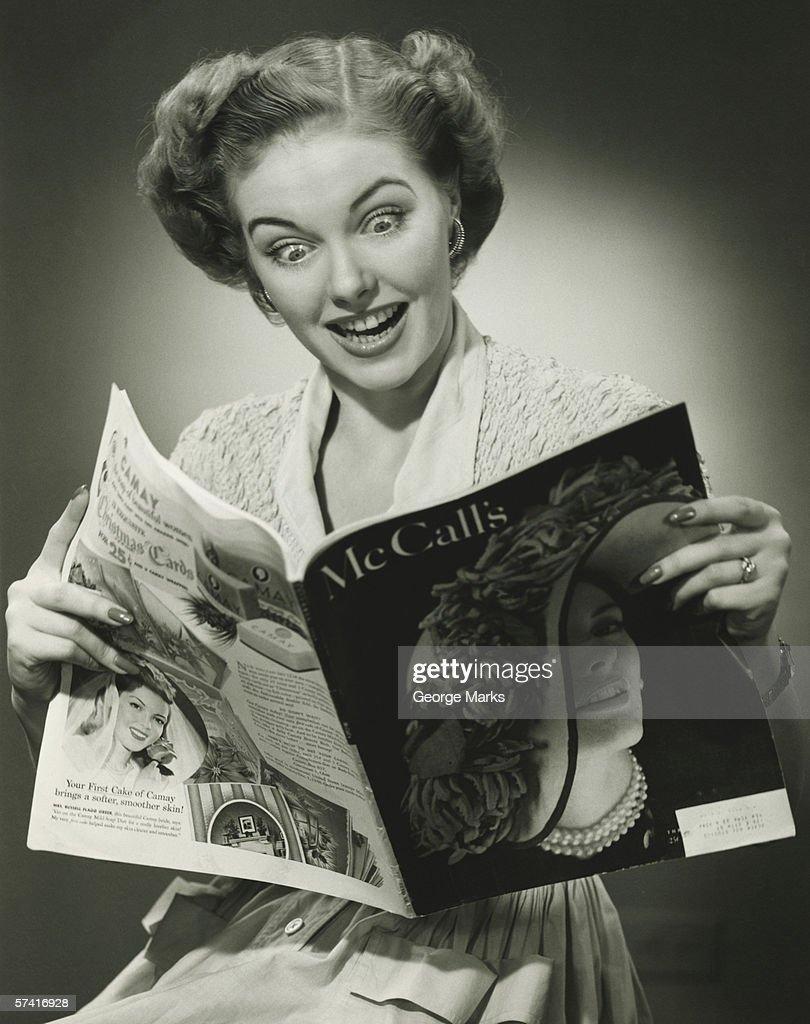 Woman looking surprised, reading fashion magazine (B&W), (Close-up) : Stock Photo