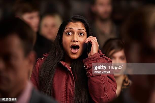 woman looking surprised, while on the phone - goed nieuws stockfoto's en -beelden