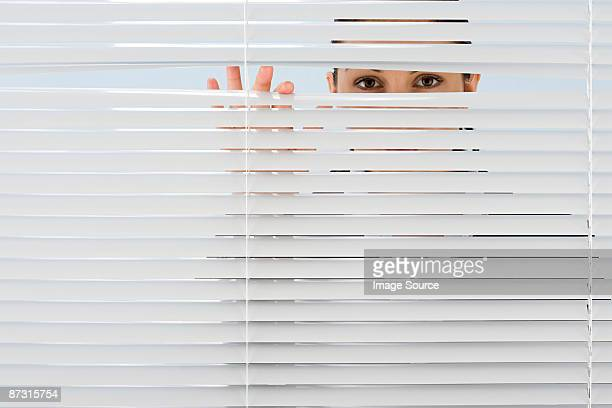 Woman looking though blinds
