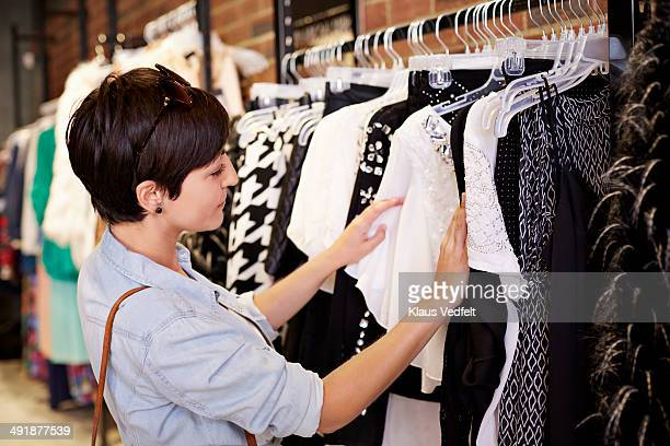 Woman looking threw clothes in fashion shop