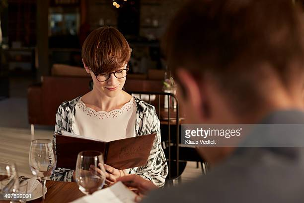 Woman looking threw menu at restaurant