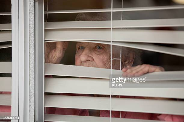 Woman looking throgh blinds