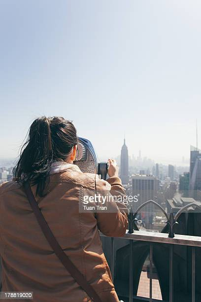 Woman looking through a coin operated binocular on Top of the Rock observation platform at the Rockefeller Center in Manhattan New York City, New...