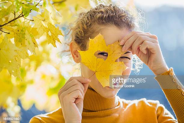 a woman looking through a hole in a leaf she's holding up to her face - human body part stock pictures, royalty-free photos & images