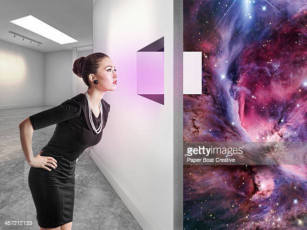 woman looking through a window to another universe - bending over stock pictures, royalty-free photos & images