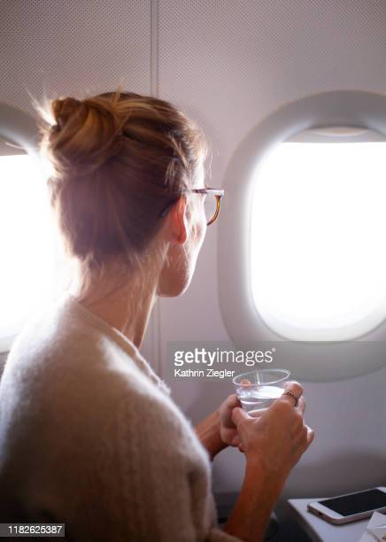 woman looking through airplane window, holding a glass of water - rodete fotografías e imágenes de stock