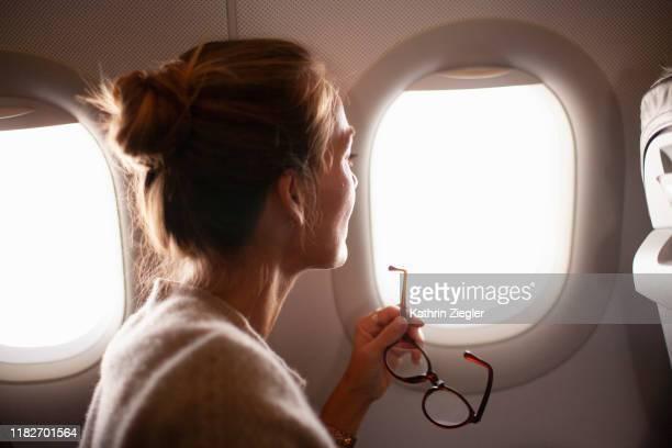 woman looking through airplane window, holding reading glasses - travel stock-fotos und bilder