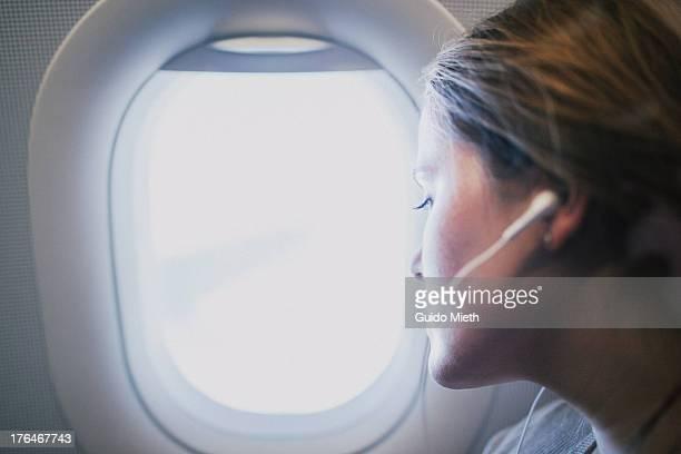 Woman looking through airplane window.