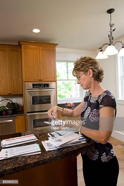 woman looking through bills  - alleen één oudere vrouw stockfoto's en -beelden