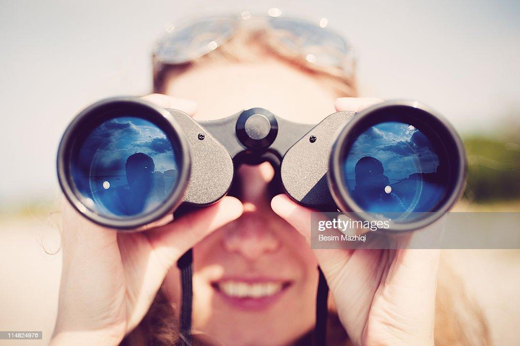 Woman looking through binocular : Stock-Foto