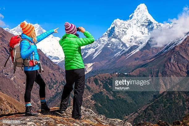 Woman looking through binoculars at Ama Dablam, Mount Everest Region