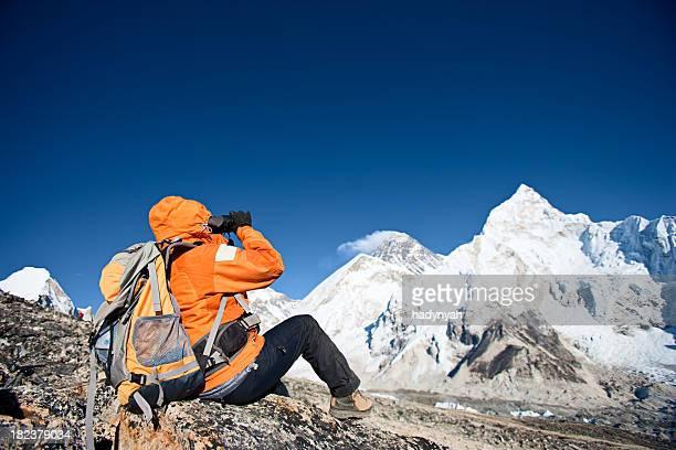 Woman looking through binoculars at Mount Everest