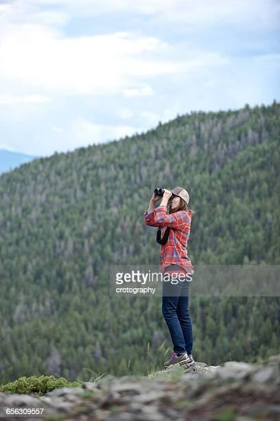 Woman looking through binoculars, Colorado, America, USA
