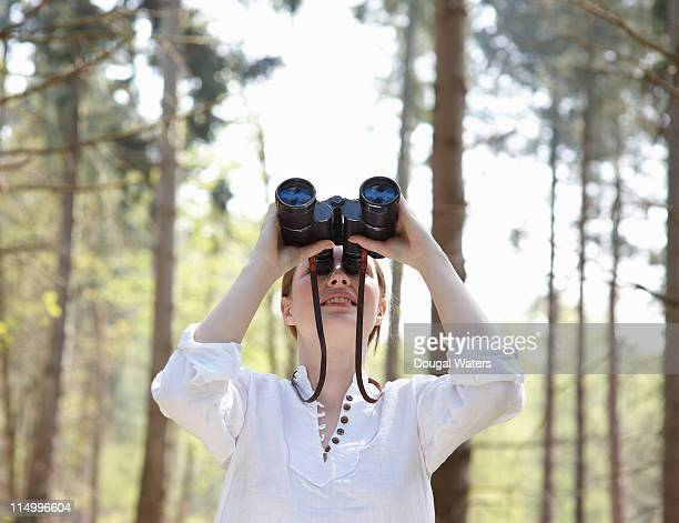 Woman looking through binoculars in forest.