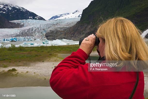 Woman looking through binoculars, Mendenhall Glacier, Juneau, Alaska, USA MR