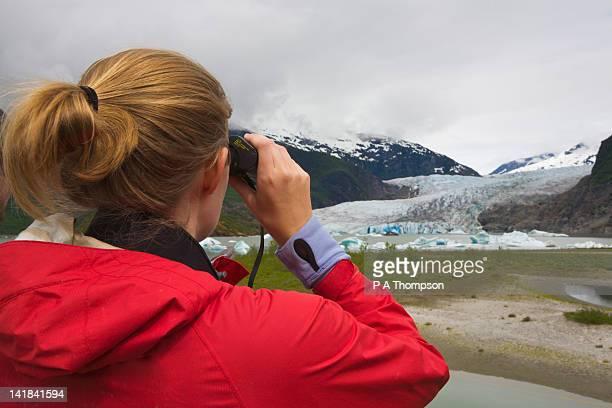 Woman looking through binoculars, Mendenhall Glacier, Juneau, Alaska, USA