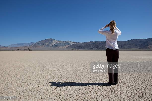 Woman looking through binoculars on a dry lake bed
