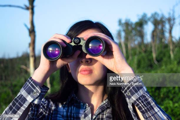 Woman Looking Through Binoculars On Sunny Day