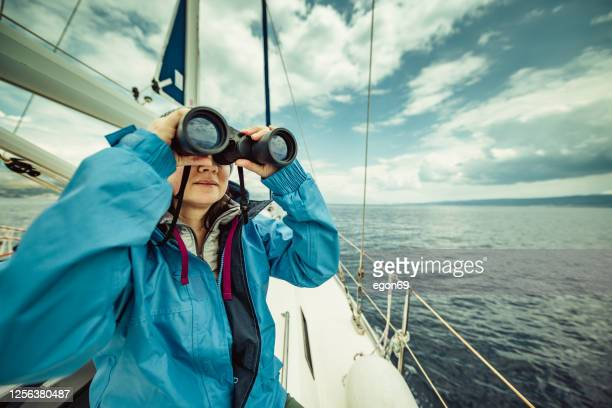woman looking through binoculars - binoculars stock pictures, royalty-free photos & images