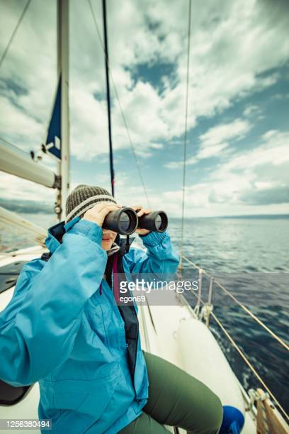 woman looking through binoculars - sailor suit stock pictures, royalty-free photos & images