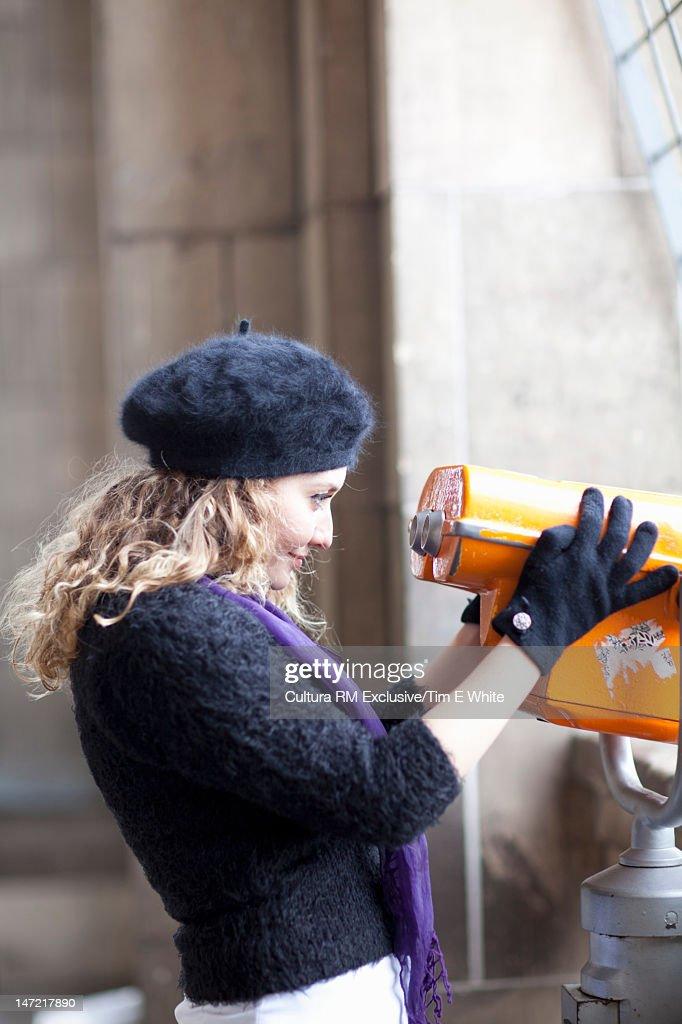 Woman looking through binoculars : Stock Photo