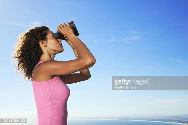 Woman looking through binoculars, side view