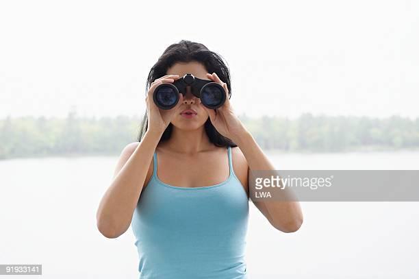 Woman Looking Through Binoculars, Standing By Lake