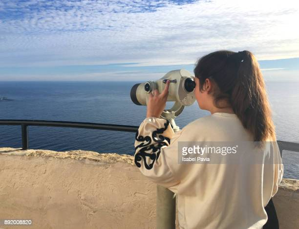Woman looking through Coin-Operated Binocular Against Sea