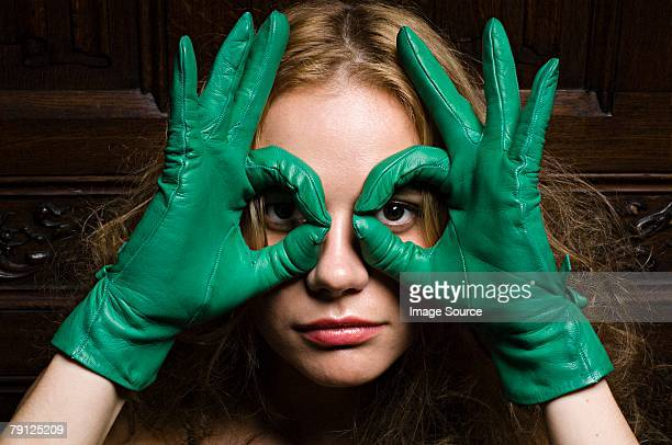 woman looking through fingers in green gloves - leather glove stock pictures, royalty-free photos & images