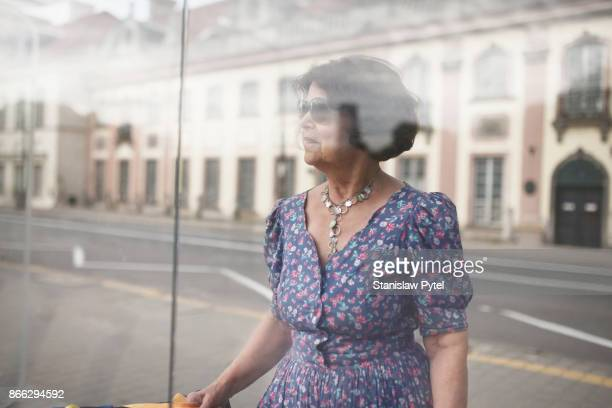 Woman looking through glass at city