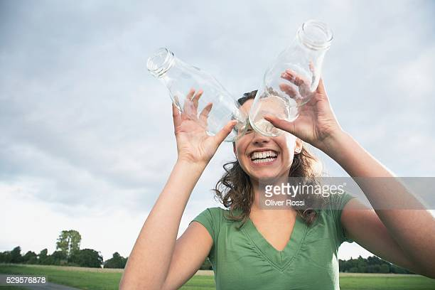 Woman Looking Through Glass Bottles