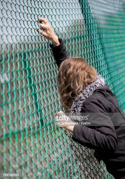 woman looking through green chainlink fence - brezinska stock pictures, royalty-free photos & images
