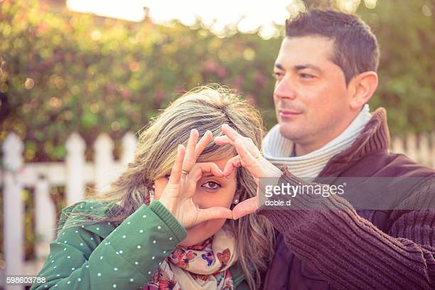 Woman looking through heart shape made with hands