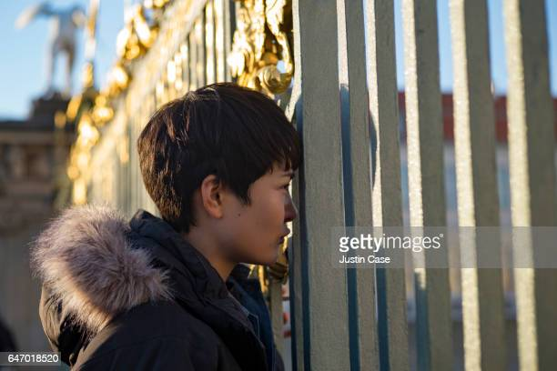woman looking through iron gates of city castle